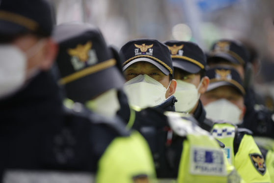 Masked police in Seoul, South Korea yesterday