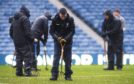 Ground staff tend to the waterlogged Ibrox pitch