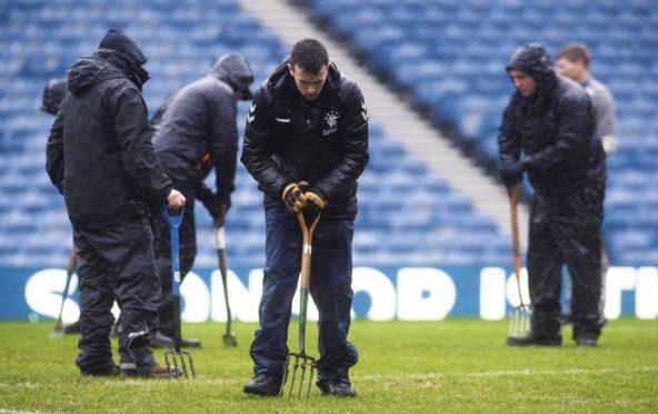 Ground staff tend to the waterlogged Ibrox pitch