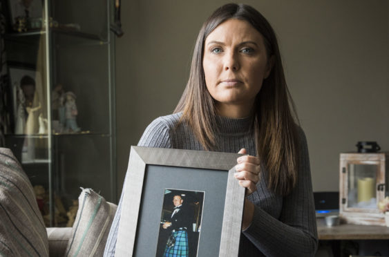 Natalie McKeown with a photograph of her father John Woods
