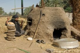 A labourer baking bread in a mud oven in Luxor, Egypt