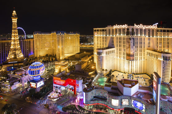 The dazzling neon lights of the Las Vegas Strip illuminate the hotels, fountains, casinos and eateries