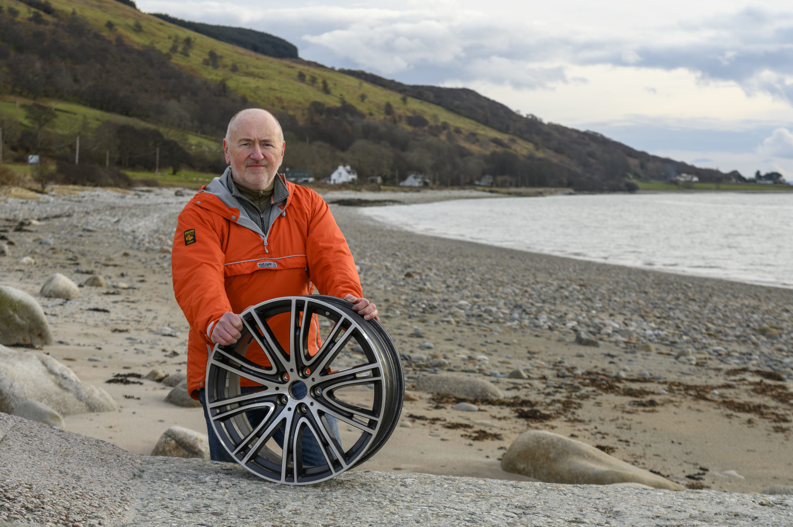 Cameron Park on Pirnmill beach, Arran, with the car wheel which was damaged by a pothole