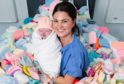Midwife Lorna McGregor with newborn baby Aria Murray in birthing pool full of baby hats at the Queen Elizabeth University Hospital in Glasgow