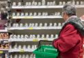 A shopper at empty soap and hand sanitiser shelves              at Asda in Toryglen, Glasgow