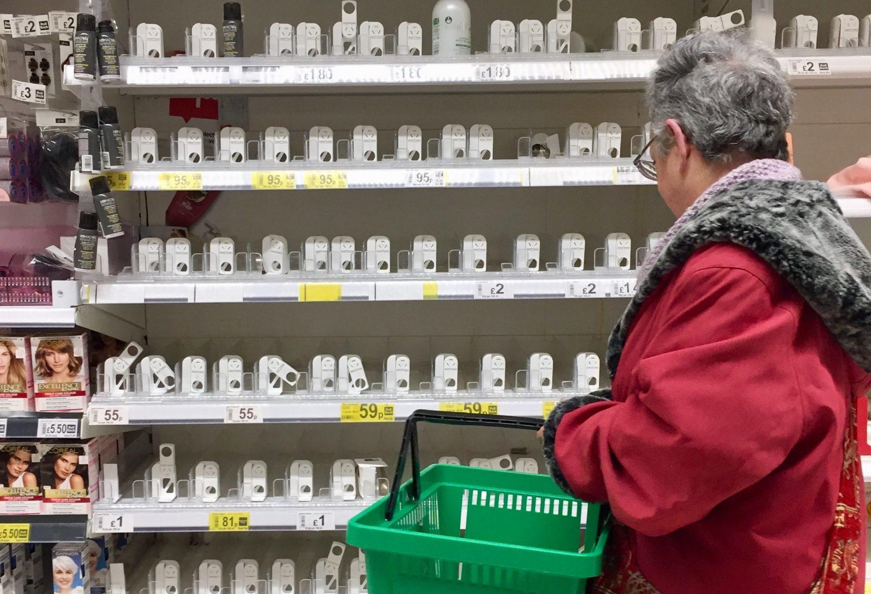 A shopper at empty soap and hand sanitiser shelves              at Asda in Toryglen, Glasgow
