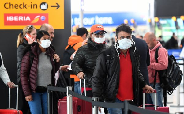 Travellers in masks queue at Heathrow airport in London as air travel grinds to a halt and nations                  across the world lock down their borders due to the coronavirus pandemic