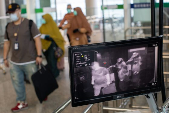 Travellers walk past a thermal scanner at the arrival terminal of Hong Kong airport