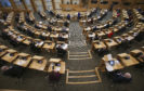 MSPs social distancing with every second seat removed at Holyrood today