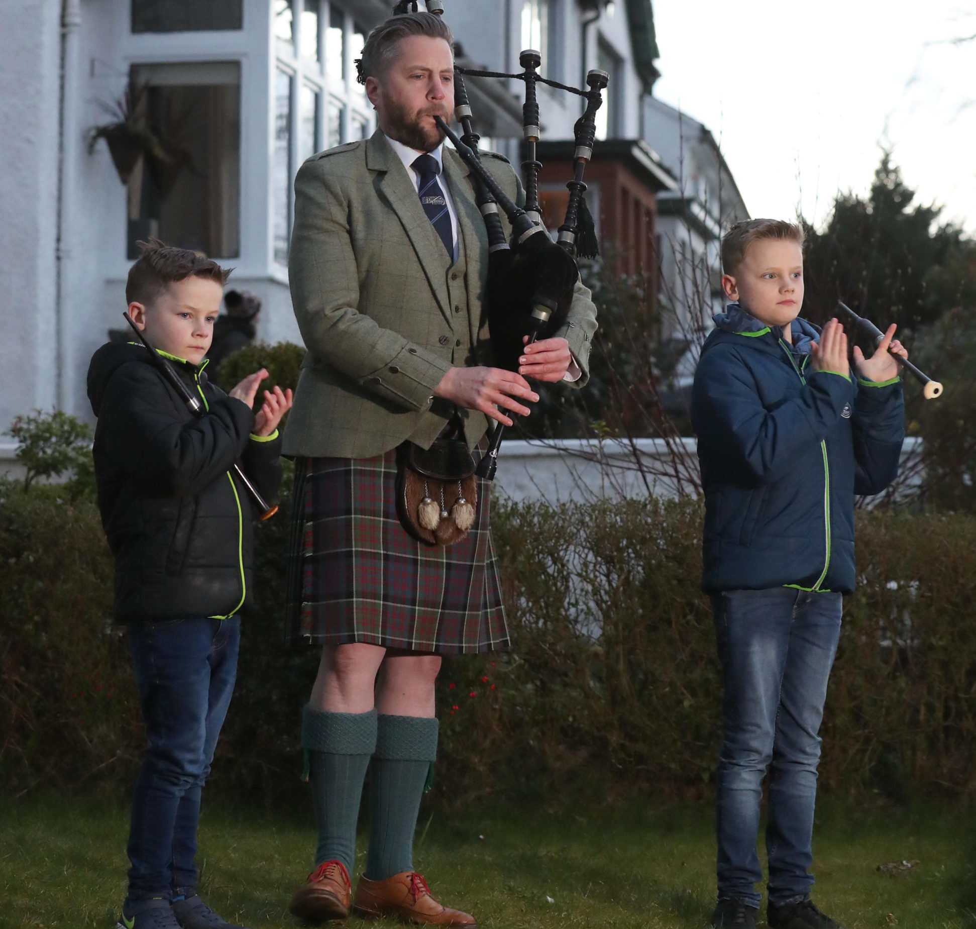 Finlay MacDonald plays the pipes at his home in Glasgow alongside sons Elliott, ten, and Fionn, eight to salute local heroes on Thursday
