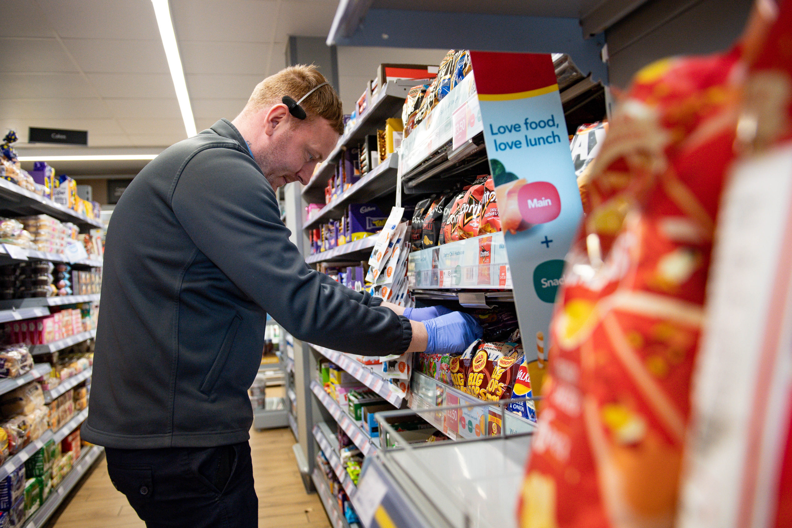 A shop worker stacks shelves whilst wearing PPE at a Co-op shop