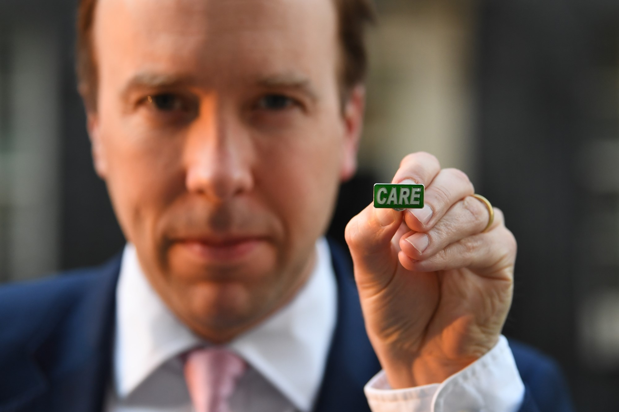 """Matt Hancock showing the new 'Care' badge, described as a """"badge of honour"""""""