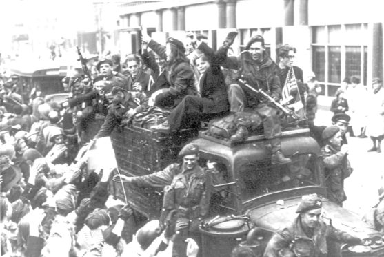 Danes cheer – and some even ride with – British troops as they drive through the streets of Copenhagen in May 1945