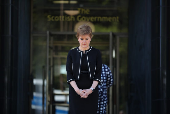 First Minister Nicola Sturgeon stands outside St Andrew's House in Edinburgh to observe a minute's silence in tribute to the NHS staff and key workers who have died during the coronavirus outbreak.
