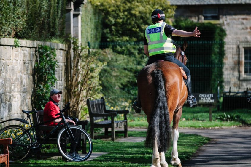 Police on horseback patrolling Pollok Park in Glasgow, asking people to move along if                         they are sitting down yesterday