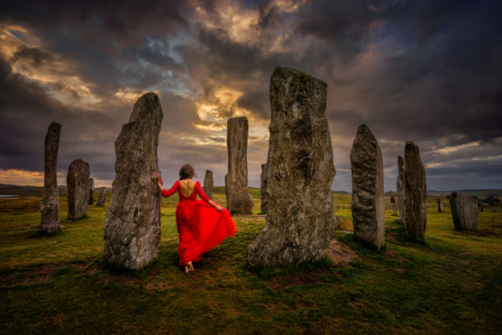 A lady in red at the mysterious Callanish Stones on Lewis