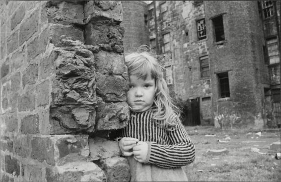 A little girl plays in the Gorbals, in Glasgow, before the stricken tenements were razed