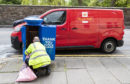A postman empties one of the specially decorated postboxes in Edinburgh painted blue in support of NHS workers and carers