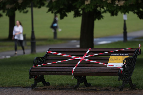 A taped off park bench as the UK continues in lockdown