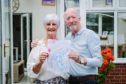 Lorna and Philip Begley with granddaughter Orla's drawing of newborn twins