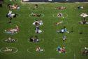 People sit inside social distancing markers at the Domino Park in Brooklyn