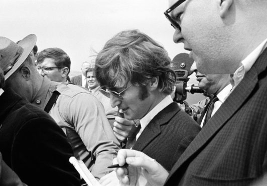 John Lennon is guided by a state trooper past journalists on arrival in Boston on August 11, 1966 for a US tour, amid a furore after he said the Beatles were more popular than Jesus