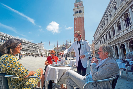 A masked waiter serves customers at the historic Cafe                Florian in Venice, Italy, on Friday as the world continues taking the first tentative steps out of lockdown