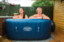Jacqueline Flanagan, right, is joined by daughter Kathleen in the hot tub at home in Bellshill, Lanarkshire