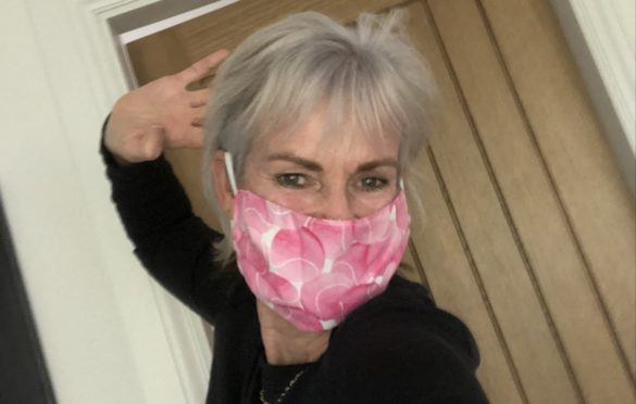 Judy Murray tries on new mask yesterday