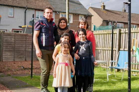One of the first families the charity helped, Yahya and Ahed Hilal are pictured with their daughters Assma, Shaima and Fatima and volunteer Home Visitor Marisa Rosie
