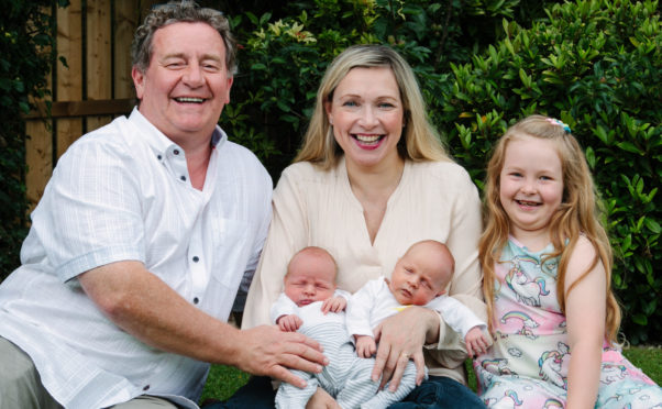 Julian Queen at home in Glasgow with her husband Graham, daughter Amelia, and newborn twin babies Louis and Harris