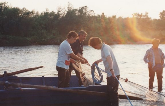 A crew haul their nets in shallow inshore waters
