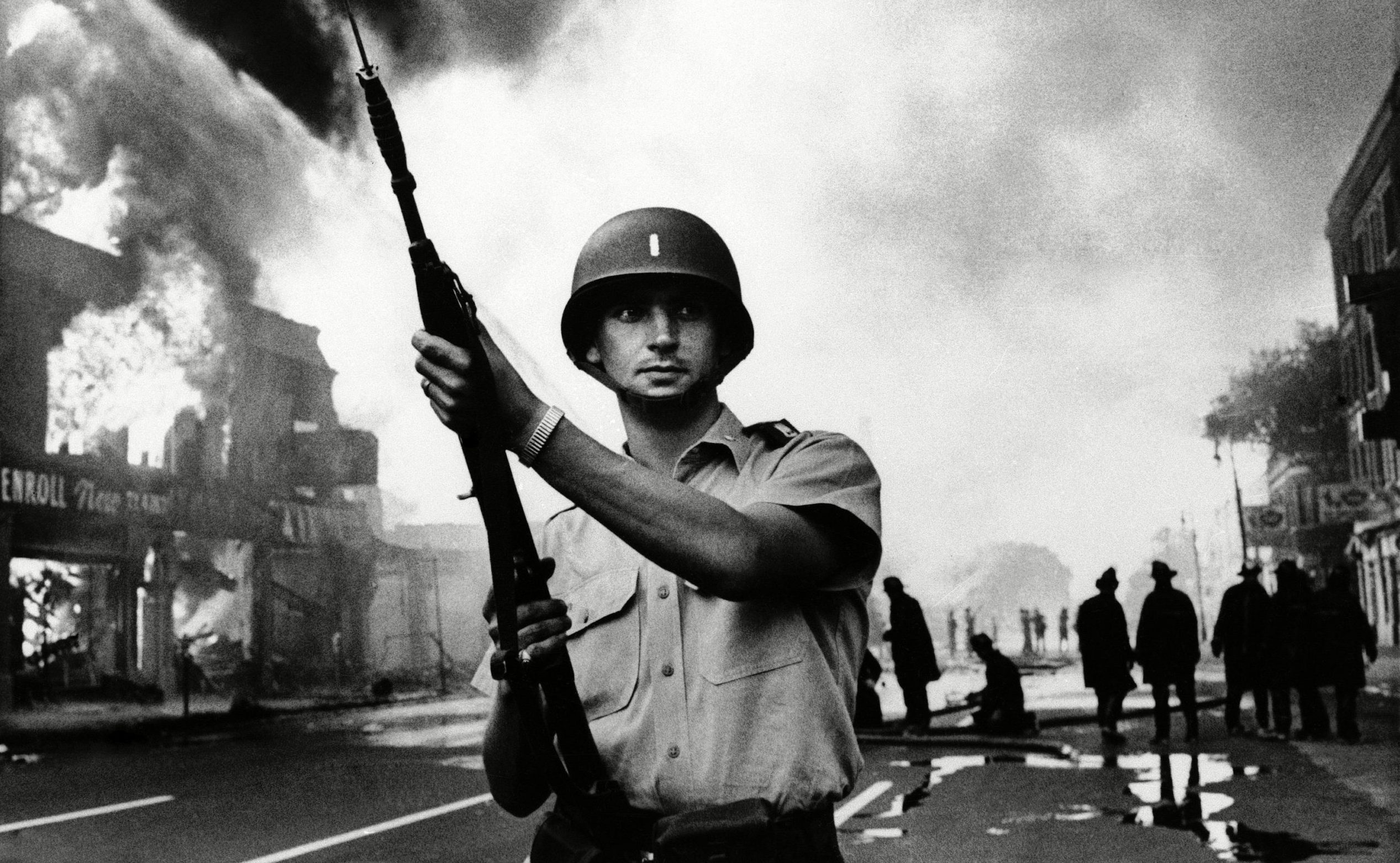A Michigan national guardsman stands at the ready as firemen battle a blaze in a riot-torn district of Detroit in July 1967