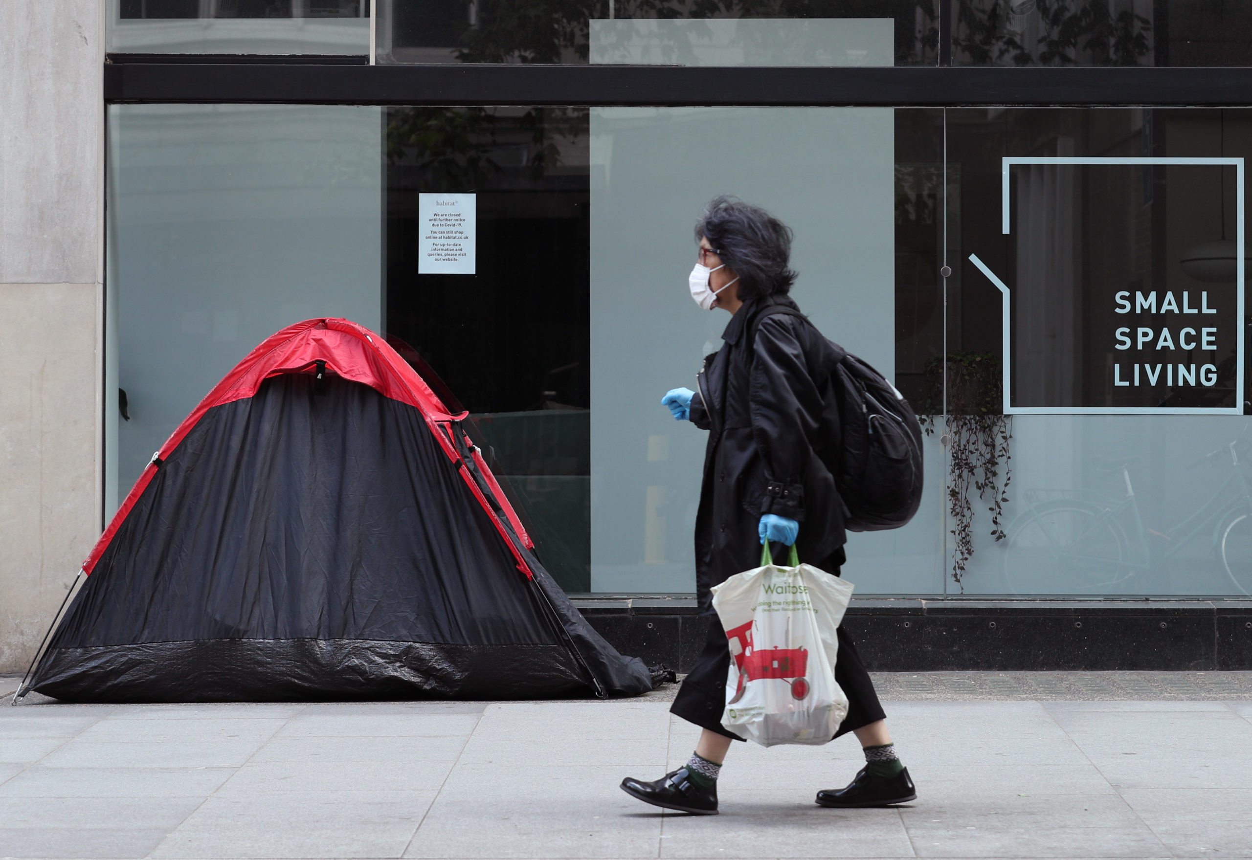 A woman walking past a homeless person's tent in London