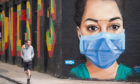 A man looks at a mural showing a nurse wearing personal protective equipment (PPE) in Shoreditch, east London