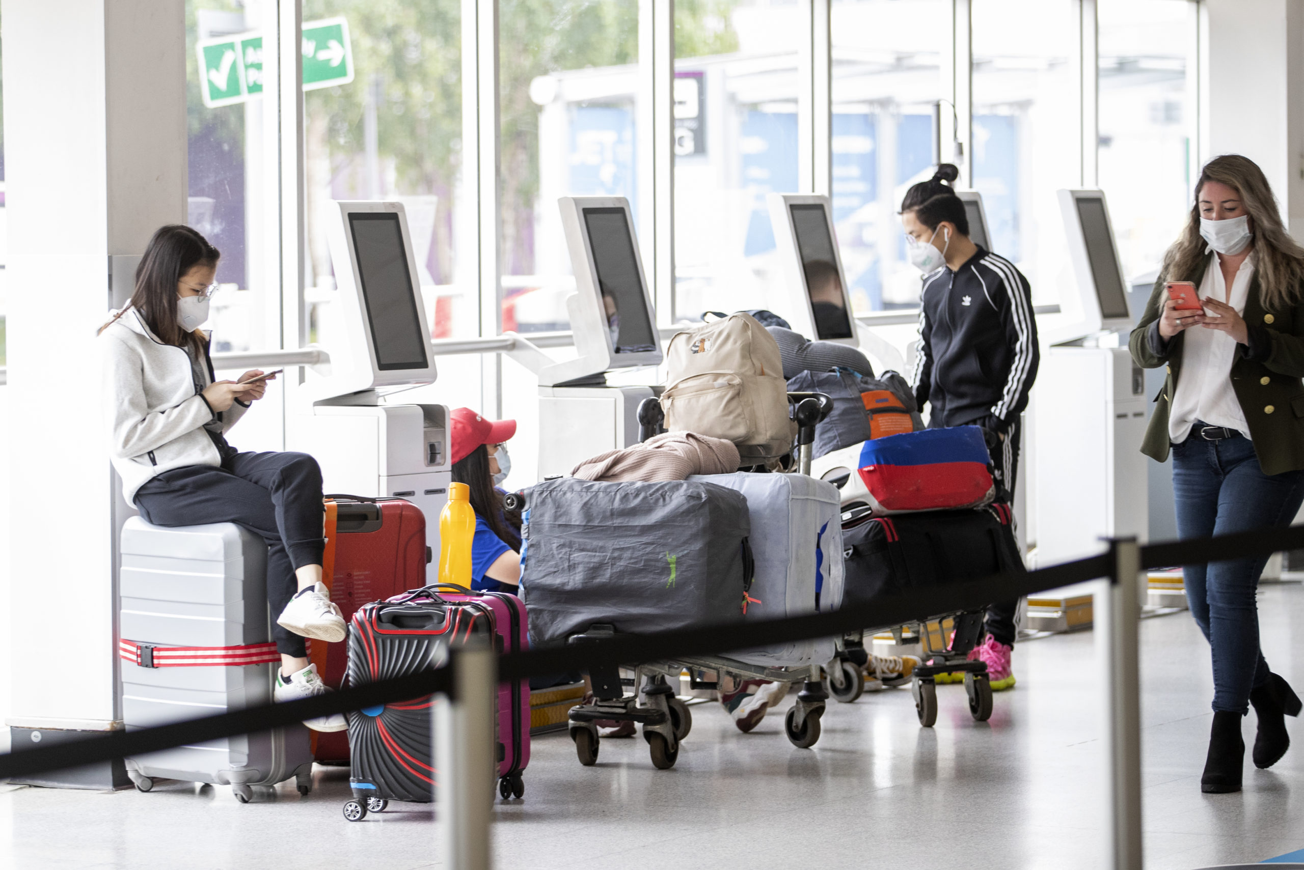 Passengers wearing protective face masks wait at the check-in area of Edinburgh Airport