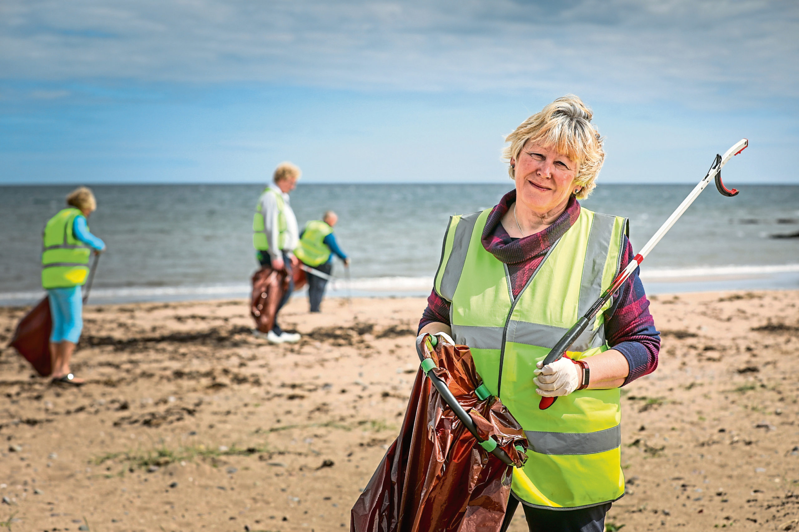 Wendy Murray and fellow volunteers from East Haven Together pick up litter dropped on the beach