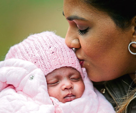 Ashvine, fully recovered, kisses her baby daughter Ashika Evie, who was born six weeks early