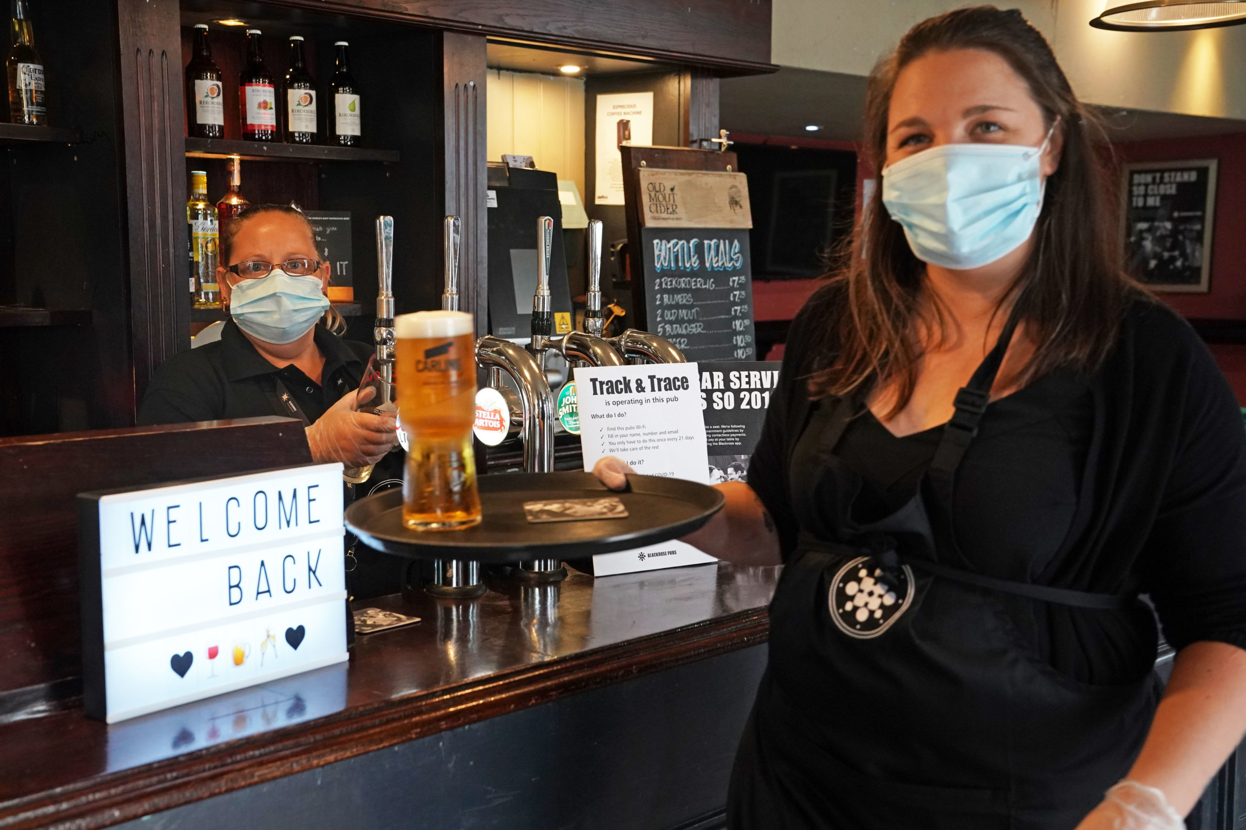 Staff at The Victoria pub in Whitley Bay welcome back customers as they serve the first pints                        post-lockdown down south