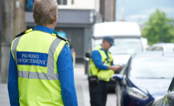 A parking officer issues a fixed penalty notice in Inverness