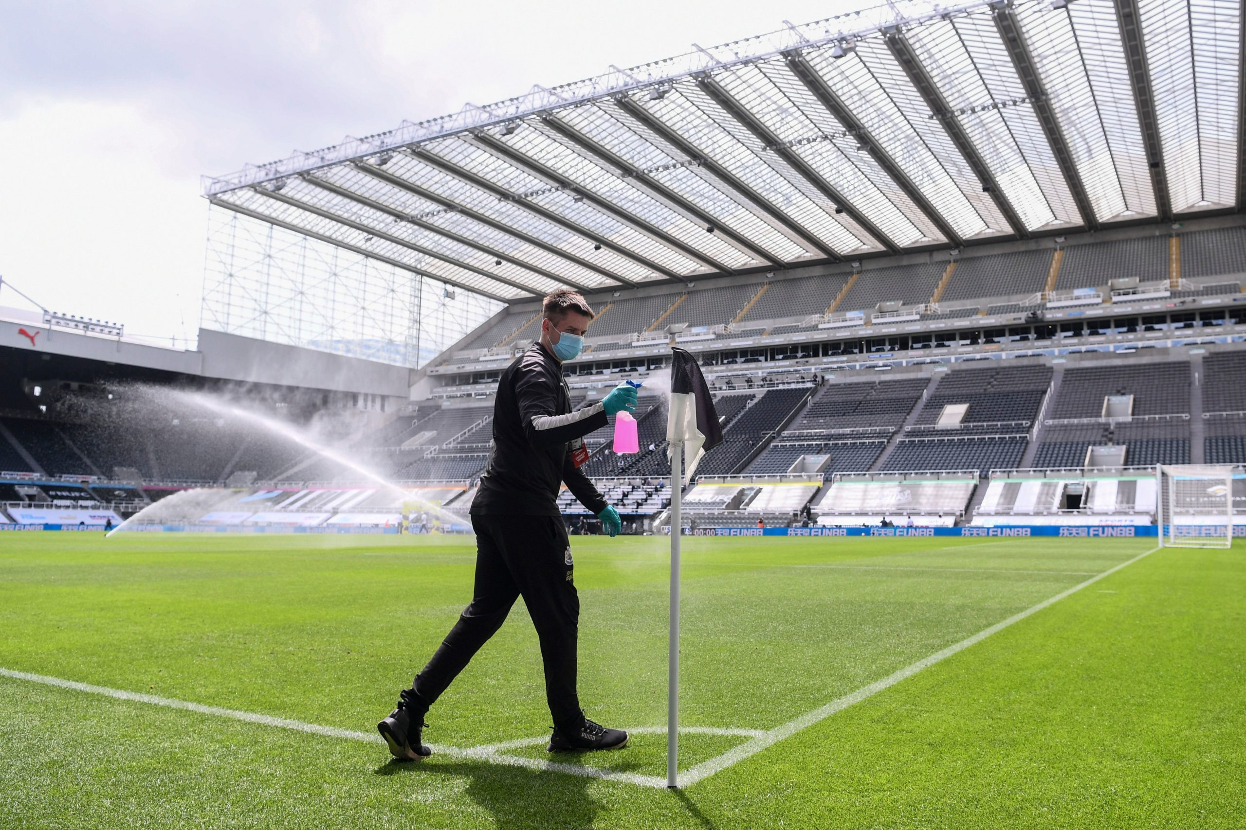 A member of the St James' Park grounds staff disinfects the corner flag before the Newcastle-Sheffield United match is played behind closed doors last month