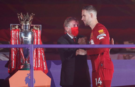 Sir Kenny congratulates Jordan Henderson as the Liverpool captain gets the Premier League trophy