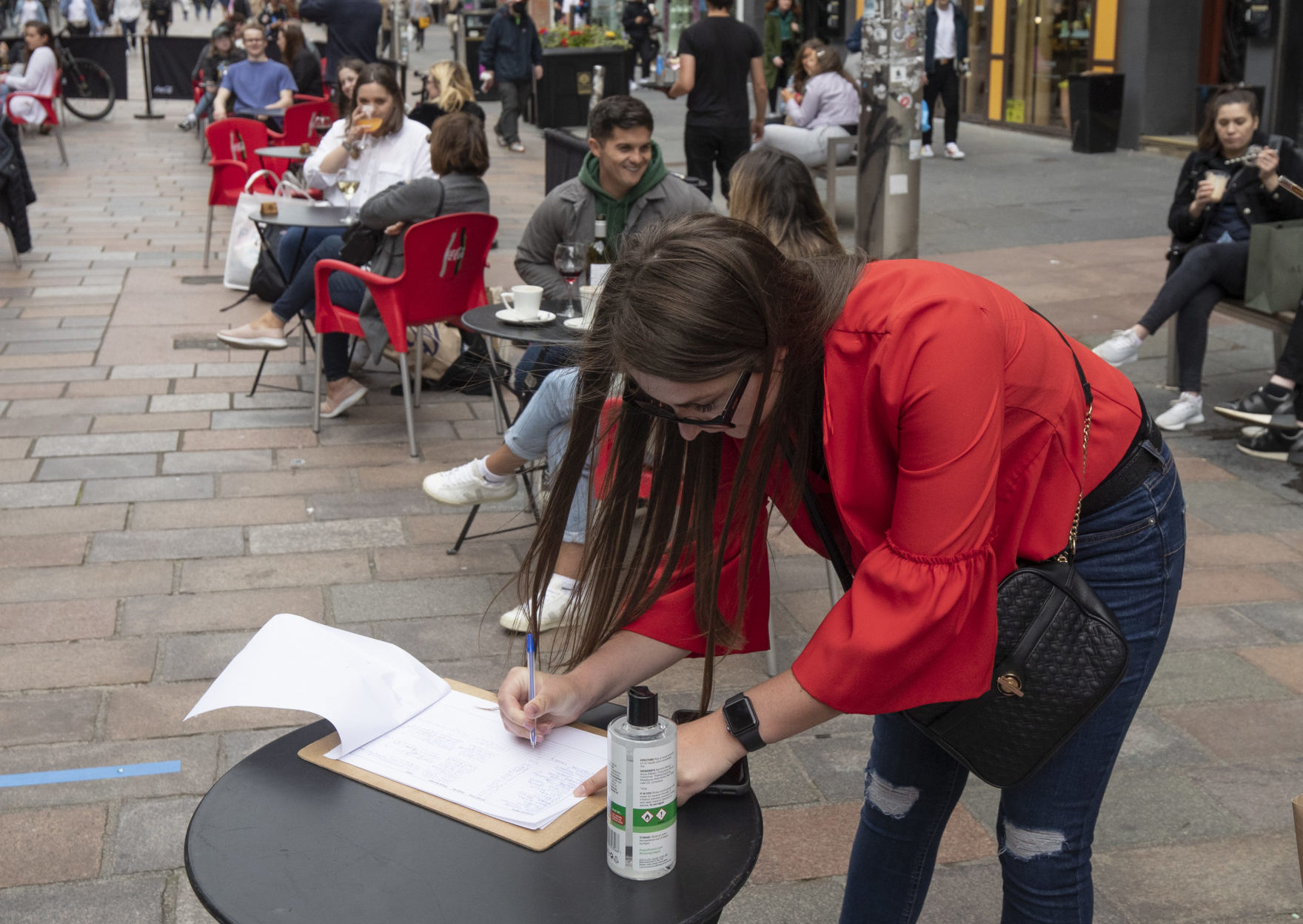 A customers fills in their contact details at the Americian NY Grill's outdoor drinking and eating area on Buchanan Street, Glasgow