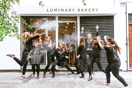Team members celebrate the success of Luminary Bakery, which helps disadvantaged women and won the Duchess of Sussex's support