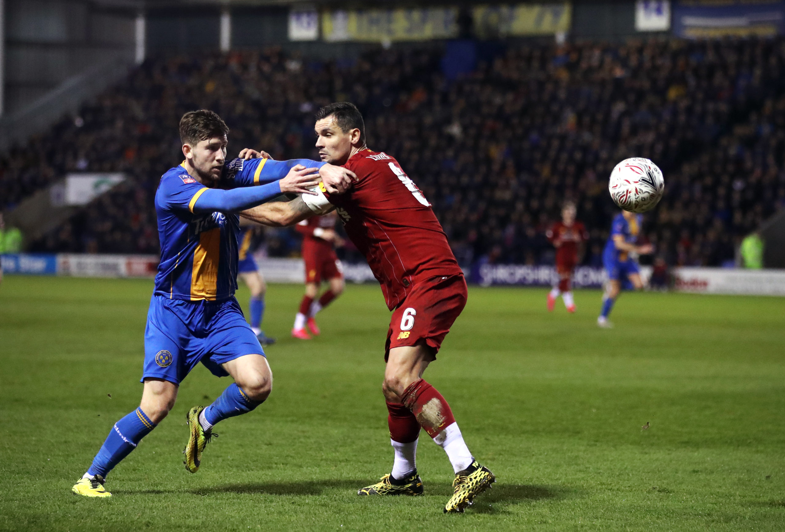 Callum Lang tussles with Dejan Lovren during Shrewsbury Town's FA Cup fourth-round tie with Liverpool in January
