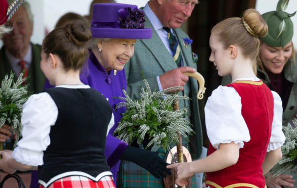 The Queen receives a posy at the Braemar Highland Gathering in September last year