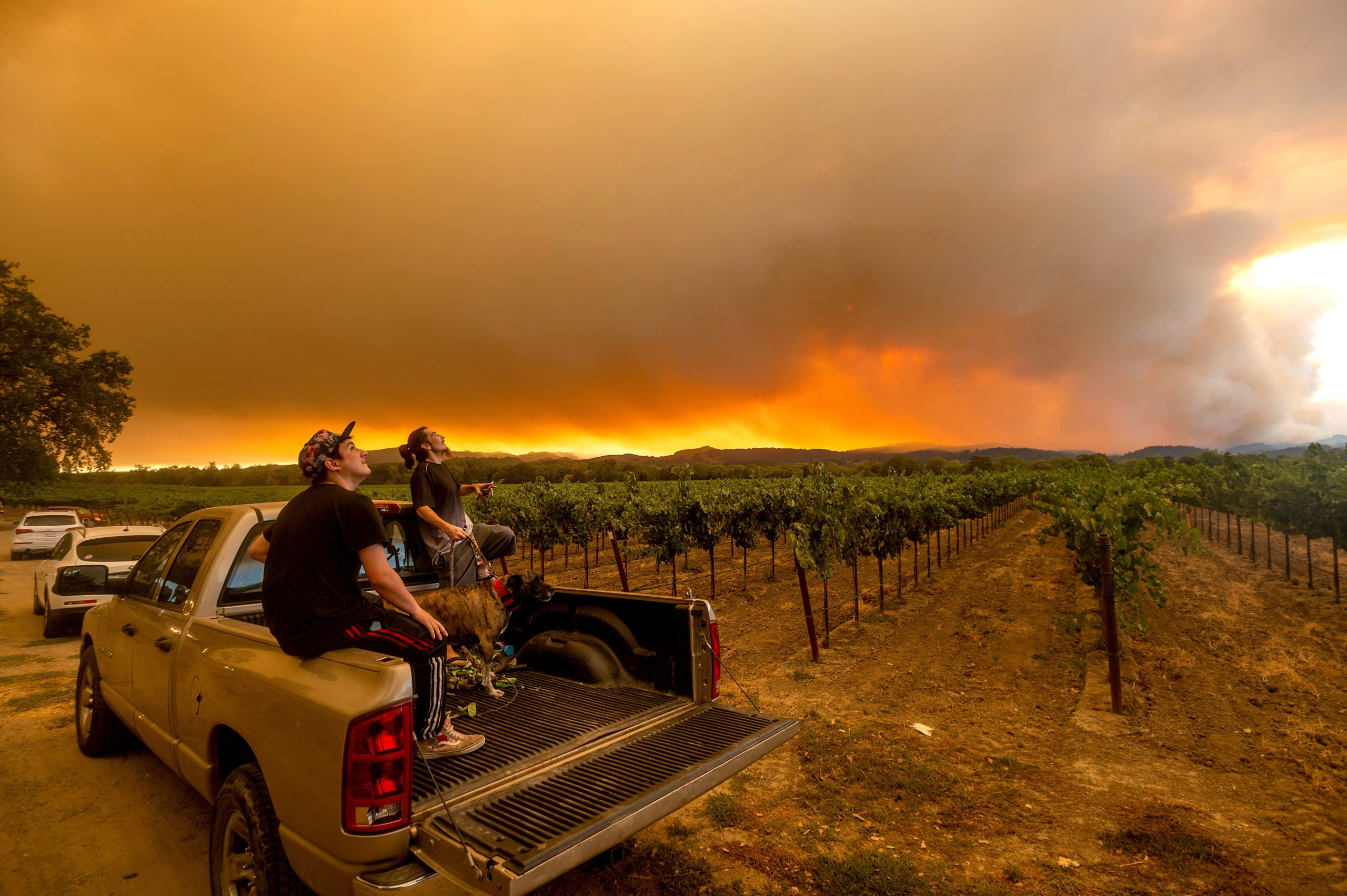 Locals watch as a plume of red smoke from the wildfires rises in the sky above Healdsburg, California