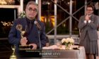 Dan Levy, right, watches as dad Eugene accepts Emmy award