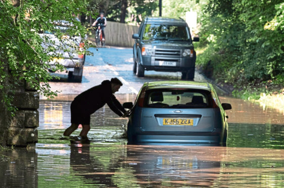 Mandatory Credit: Photo by Tina Norris/Shutterstock (10742192g) A man abandons his car after driving it through flood water and becoming stuck on Station Road, Oakley in Fife Flash flooding, Fife, UK - 12 Aug 2020