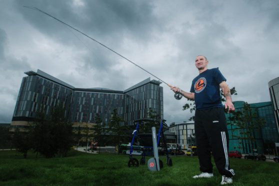 Injured angler Robbie Bell casting his fly rod outside the QEUH in Glasgow